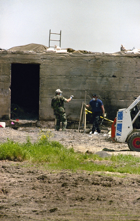 . Investigators clear debris from the area in front of the concrete blockhouse at the destroyed Branch Davidian compound near Waco, Texas on Monday, April 26, 1993. Independent arson investigators supported FBI claims that members of the cult started a fire that consumed their compound. (AP Photo/Roberto Borea)
