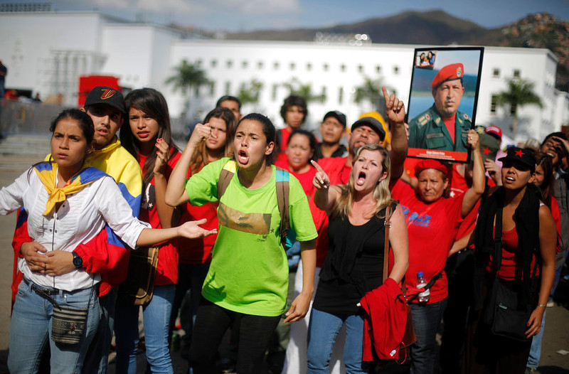 . Supporters of Venezuela\'s late President Hugo Chavez protest over others cutting the line as they wait to view his body in state at the Military Academy in Caracas, March 7, 2013. Venezuelans flocked to pay tribute to Chavez two days after he died of cancer.   REUTERS/Tomas Bravo