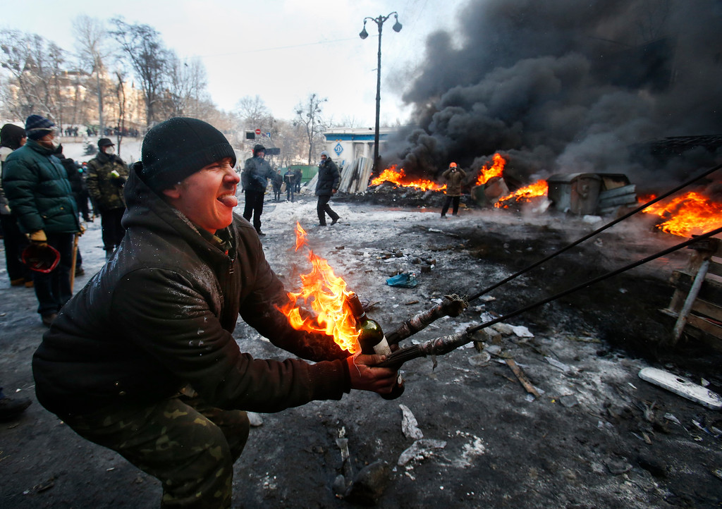 . Protesters use a large slingshot to hurl a Molotov cocktail at police in central Kiev, Ukraine, Thursday Jan. 23, 2014. (AP Photo/Sergei Grits, File)