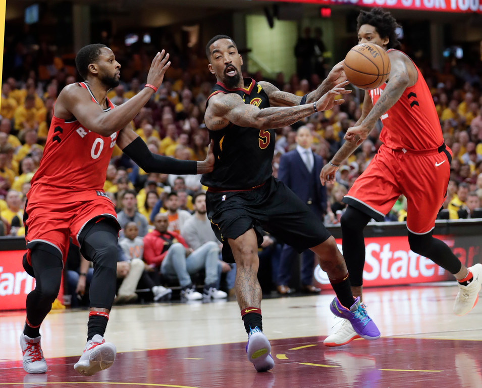 . Cleveland Cavaliers\' JR Smith (5) passes against Toronto Raptors\' CJ Miles (0) and Lucas Nogueira in the first half of Game 4 of an NBA basketball second-round playoff series, Monday, May 7, 2018, in Cleveland. (AP Photo/Tony Dejak)