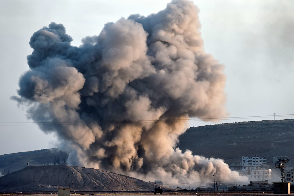. Smoke rises from the impact of an airstrike next to the hill where Islamic State (IS) militants had placed their flag in the Syrian town of Ain al-Arab, known as Kobane by the Kurds, seen  from the Turkish-Syrian border in the southeastern village of Mursitpinar, Sanliurfa province, on October 8, 2014. The Pentagon warned on October 8, 2014 US air power on its own could not prevent Islamic State jihadists from capturing the Syrian border town of Kobane, even as US warplanes kept up bombing raids in the area.ARIS MESSINIS/AFP/Getty Images