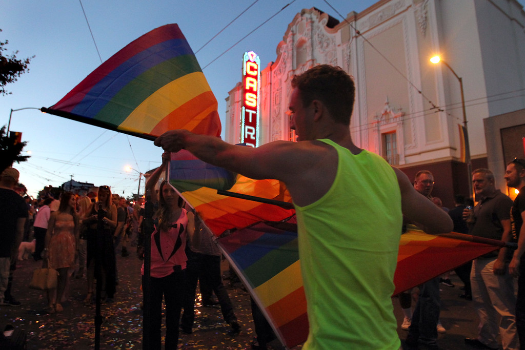 . Katie Nash, center, and photographer Colson Griffith, of San Francisco, set up a backdrop with the gay pride flag as they celebrate the Supreme Court\'s rulings on Proposition 8 and the Defense of Marriage Act in the Castro district in San Francisco, Calif., on Wednesday, June 26, 2013. (Ray Chavez/Bay Area News Group)