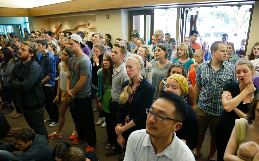 . People stand in the foyer during a prayer service at the First Free Methodist Church Thursday, June 5, 2014 at Seattle Pacific University in Seattle, where a shooting took place Thursday afternoon.(AP Photo/Ted S. Warren)