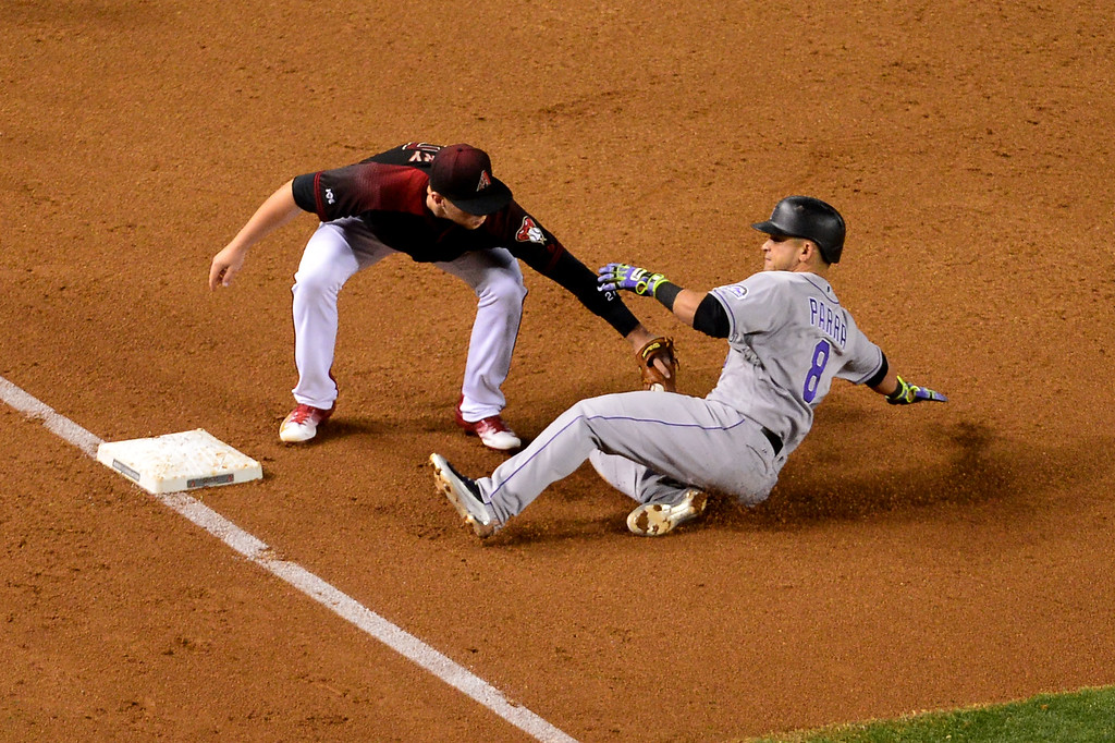 . Gerardo Parra #8 of the Colorado Rockies is tagged out while attempting to steal third base by Brandon Drury #27 of the Arizona Diamondbacks in the third inning at Chase Field on April 30, 2016 in Phoenix, Arizona. (Photo by Jennifer Stewart/Getty Images)