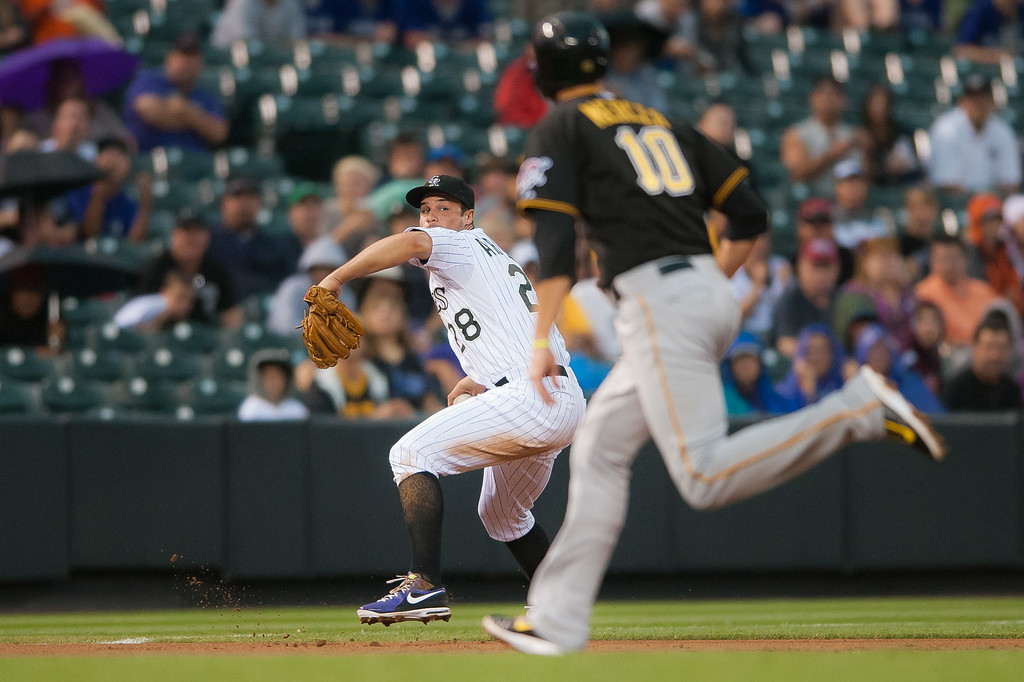 . Nolan Arenado #28 of the Colorado Rockies sets to put out the runner at first base  as Jordy Mercer #10 of the Pittsburgh Pirates advances to third base during a game at Coors Field on July 26, 2014 in Denver, Colorado.  (Photo by Dustin Bradford/Getty Images)