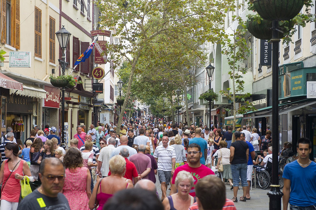 """. Tourist walk on Main street in Gibraltar on August 13, 2013 as Spain today enforced tight border checks in a growing row with Britain over the tiny territory and its surrounding waters. On the \""""Rock\"""" itself, defiant residents declared themselves thoroughly British, surrounded by English pubs serving fish and chips, Royal Mail letter boxes, bright red telephone cabins and the occasional monkey.   MARCOS MORENO/AFP/Getty Images"""