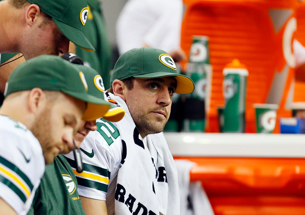 . Green Bay Packers quarterback Aaron Rodgers watches the game on the bench during the first half of an NFL football game against the Detroit Lions in Detroit, Sunday, Sept. 21, 2014. (AP Photo/Paul Sancya)