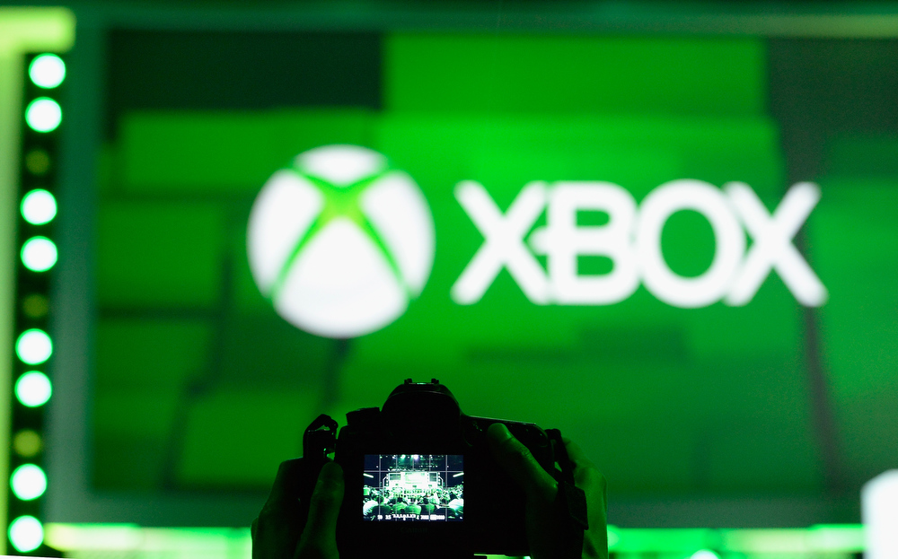 . An attendee takes a photo of the XBOX logo during the Microsoft Xbox news conference at the Electronic Entertainment Expo at the Galen Center on June 10, 2013 in Los Angeles, California. Thousands are expected to attend the annual three-day convention to see the latest games and announcements from the gaming industry. (Photo by Kevork Djansezian/Getty Images)