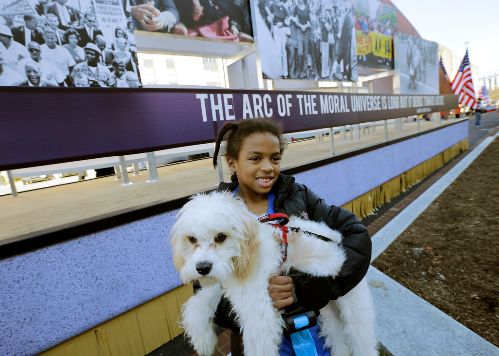 ". Arianna Dorman of Fort Washington, Md., holds her dog ""Luke,\"" as she poses for a picture with the civil rights movement float prepared for the 57th Presidential Inaugural Parade, Sunday, Jan. 20, 2013 in Washington. Thousands are planning to march in the 57th Presidential Inauguration parade after the ceremonial swearing-in of President Barack Obama on Monday. (AP Photo/Alex Brandon)"