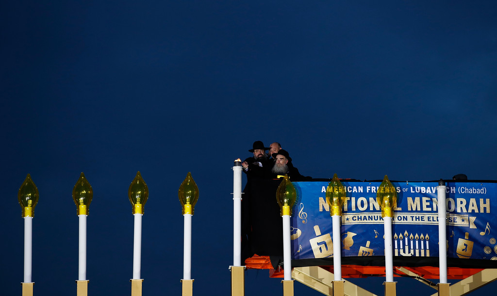 . From left, Rabbi Levi Shemtov, National Economic Director Gary Cohn, and Rabbi Abraham Shemtov light the Menorah during the annual National Menorah Lighting, in celebration of Hanukkah, on the Ellipse near the White House in Washington, Tuesday, Dec. 12, 2017. (AP Photo/Carolyn Kaster)