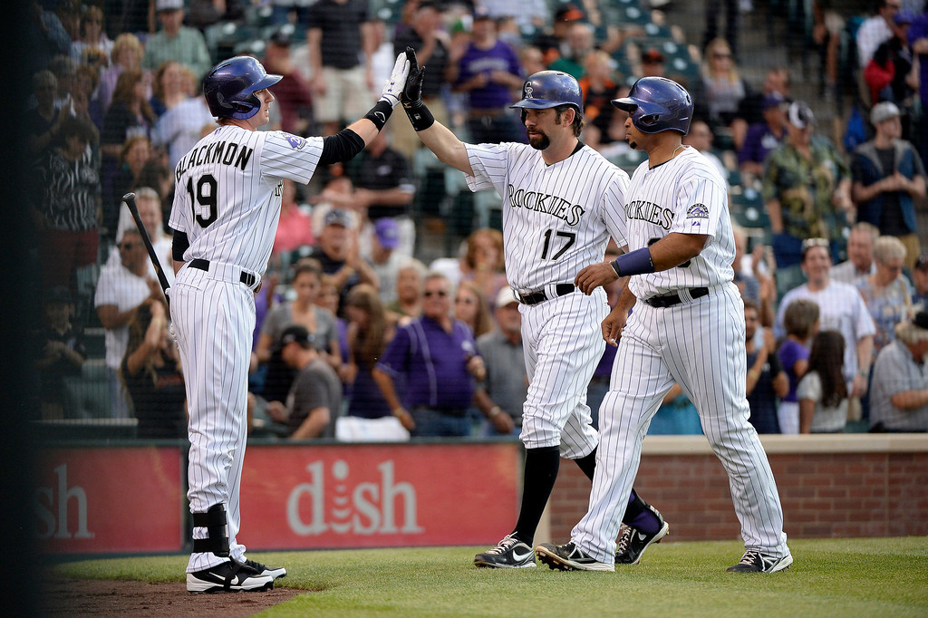 . Todd Helton (17) of the Colorado Rockies high fives Charlie Blackmon (19) along with Wilin Rosario (20) after hitting a two run home run off of Matt Cain (18) of the San Francisco Giants during the second inning May 16, 2013 at Coors Field. (Photo By John Leyba/The Denver Post)