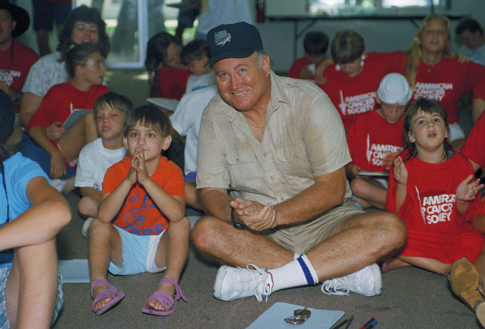 Description of . Gulf war hero, former General H. Norman Schwarzkopf claps and sings along with 'I Can Be the Best I Can Be,' during a visit to a suburban Tampa camp for kids with Cancer, Friday, August 7, 1999. R.O.C.K. camp, Reach Out To Cancer, Kids, in a week long summer camp for kids with Cancer paid for by the American Cancer Society. Schwarzkopf said ?If I made one of these kids feel a little better today, it?s worth all the time in the world,? (AP Photo/Karan Fletcher)