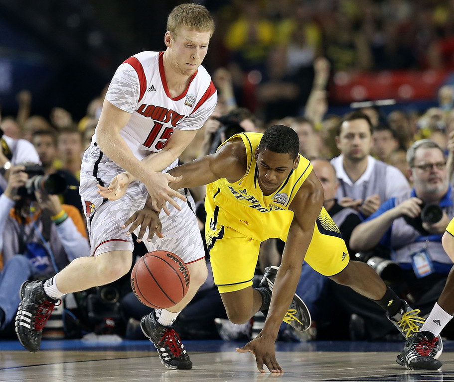 . Tim Henderson #15 of the Louisville Cardinals and Glenn Robinson III #1 of the Michigan Wolverines go after a loose ball in the first half during the 2013 NCAA Men\'s Final Four Championship at the Georgia Dome on April 8, 2013 in Atlanta, Georgia.  (Photo by Streeter Lecka/Getty Images)
