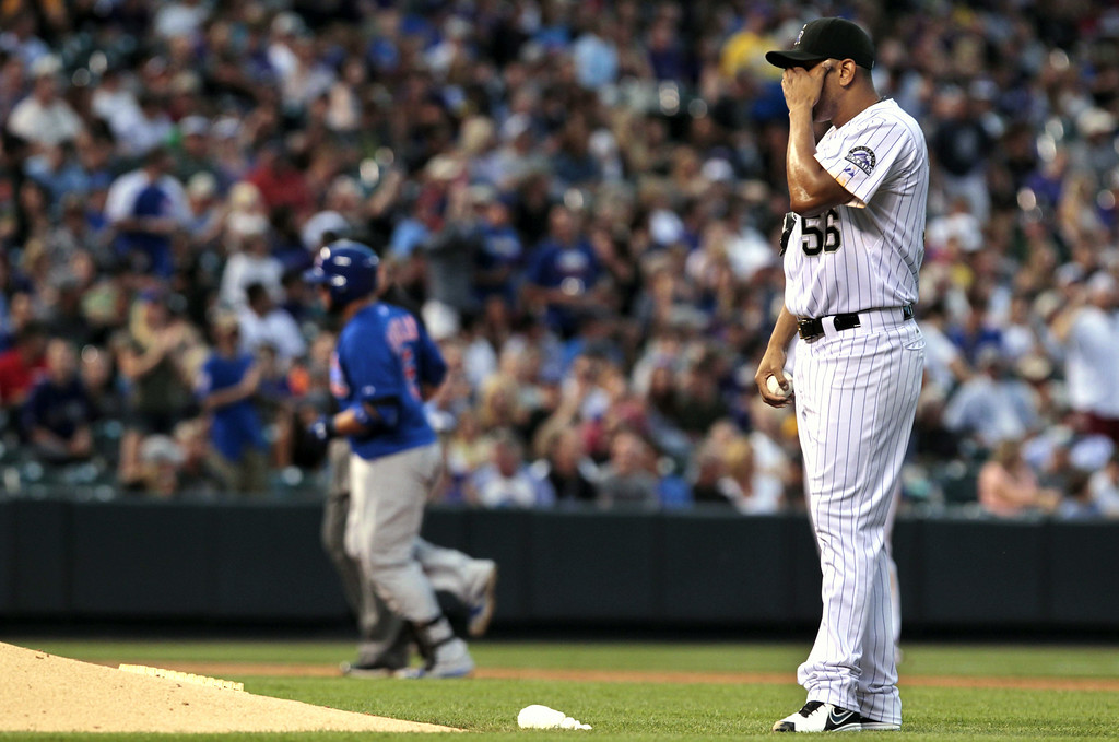 . Colorado Rockies starting pitcher Franklin Morales (56) wipes his face as Chicago Cubs\' Welington Castillo, left, circles the bases after his solo home run in the sixth inning of a baseball game in Denver on Tuesday, Aug. 5, 2014.(AP Photo/Joe Mahoney)