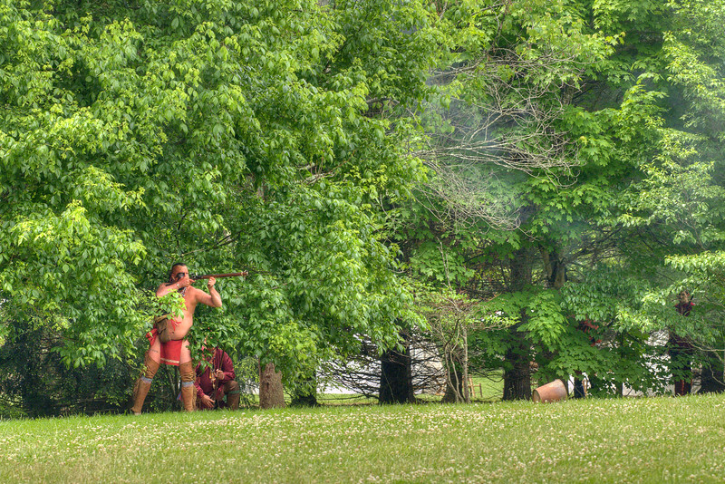 A Native American reenactor prepares to fire a rifle from the cover of the tree line during the Siege of Fort Watauga at Sycamore Shoals State Park in Elizabethton, VA on Saturday, May 17, 2014. Copyright 2014 Jason Barnette  The Siege of Fort Watauga is a two-day reenactment held each year at the recreation of the fort inside Sycamore Shoals State Historic Park. The reenactment brings in dozens of reenactors and hundreds of visitors as they tell the story of an attack on the early settlers village by Dragging Canoe, and how they successfully defended themselves. During the reenactment, the fort is open to the public with demonstrations of all areas of early settler life on the frontiers.