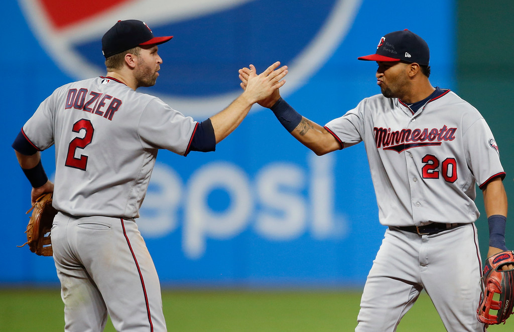 . Minnesota Twins\' Brian Dozier (2) and Eddie Rosario (20) celebrate an 8-6 victory over the Cleveland Indians in a baseball game, Tuesday, Sept. 26, 2017, in Cleveland. (AP Photo/Ron Schwane)