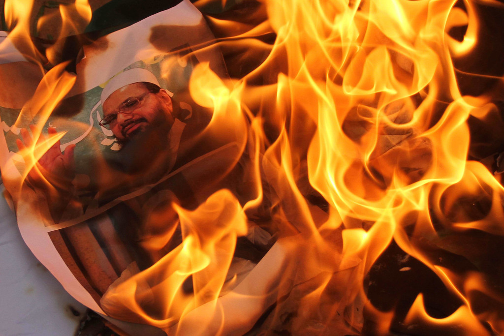 . Flames engulf a portrait of Hafiz Mohammad Saeed, chief of Jamaat-ud-Dawwa and founder of Lashkar-e-Taiba, during a protest in Ahmadabad, India, Saturday, Aug. 10, 2013. India\'s defense minister directly accused Pakistan on Thursday of killing five Indian soldiers in the disputed Himalayan region of Kashmir and suggested it could hurt peace efforts by the two countries. (AP Photo/Ajit Solanki)