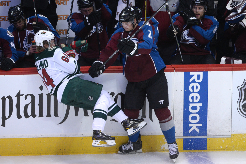 . Nick Holden (2) of the Colorado Avalanche checks Mikael Granlund (64) of the Minnesota Wild during the first period of action. The Colorado Avalanche hosted the Minnesota Wild in the first round of the NHL playoffs at the Pepsi Center on Thursday, April 17, 2014. (Photo by Karl Gehring/The Denver Post)