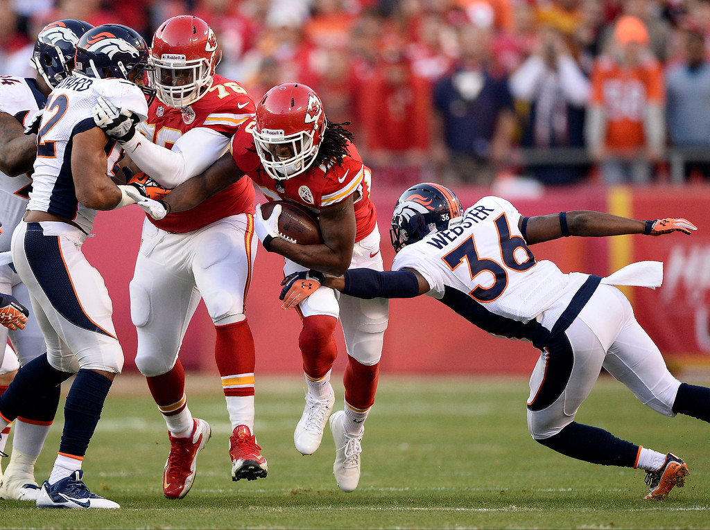 . Kansas City Chiefs running back Jamaal Charles (25) picks up a big gain as Denver Broncos cornerback Kayvon Webster (36) comes in for the tackle during the first quarter December 1, 2013 at Arrowhead Stadium.  (Photo by John Leyba/The Denver Post)