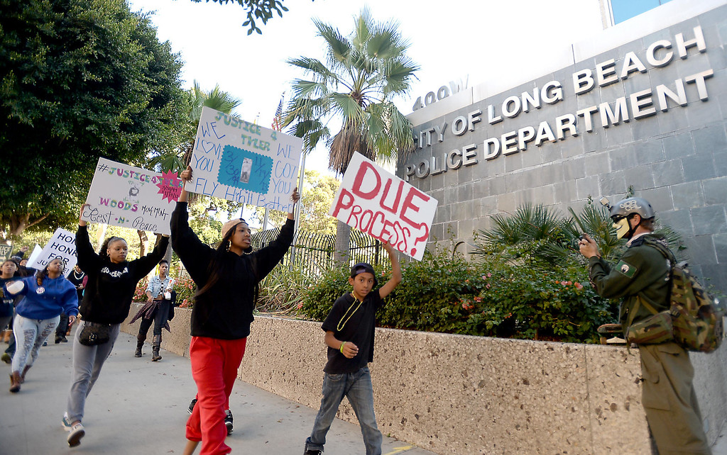 . Kyra Woods, Tyler\'s sister, in red pants, leads the march for her brother ,who was shot by the Long Beach Police Department on Nov. 19, at the rally outside the department headquarters in Long Beach on Sunday, November 24, 2013. (Photo by Sean Hiller/ Daily Breeze).