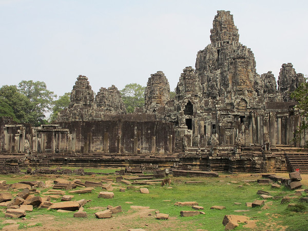 The Bayon was built in the late 12th century or early 13th century as the official state temple of the Mahayana Buddhist King Jayavarman VII and stands at the centre of Jayavarman's capital, Angkor Thom. It was the last state temple to be built at Angkor, and the only Angkorian state temple to be built primarily as a Mahayana Buddhist shrine dedicated to the Buddha.   The Bayon was revealed as a three-tiered pyramid temple after being cleared of overgrowth, with the central tower stretching to 45m in height. This central tower is topped with the largest examples of the all-facing, all-seeing enigmatic faces that litter the temple throughout. Originally the Bayon was comprised of 54 towers, each of which supported four faces — one looking to each point of the compass. Today, 49 towers remain. Theories behind the meaning of the faces have surmised that the sculptures represented King Jayavarman VII as a god-king and suggest that the 54 towers represent the 54 provinces of the realm, with the king's face looking over the entire country.  The temple is known also for two impressive sets of bas-reliefs, which present an unusual combination of mythological, historical, and mundane scenes.  Read more: http://www.virtualtourist.com/travel/Asia/Cambodia/Khett_Siem_Reab/Angkor_Wat-1202517/Things_To_Do-Angkor_Wat-Angkor_Thom-BR-2.html#ixzz1KRthf8nG