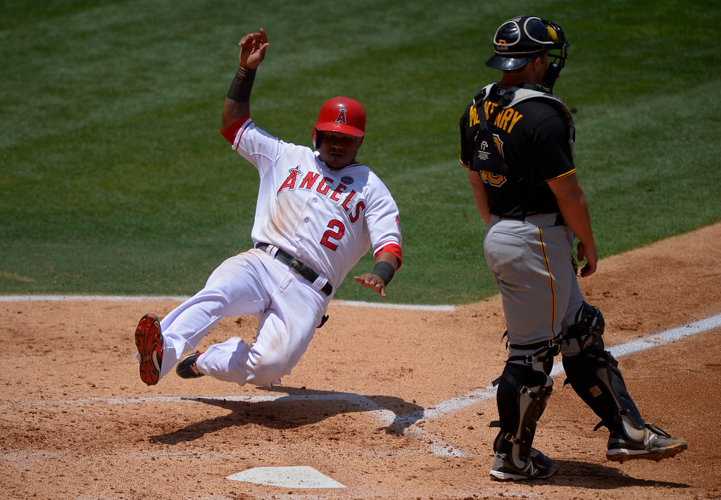 . Los Angeles Angels\' Erick Aybar, left, scores on a single by J.B. Shuck as Pittsburgh Pirates catcher Michael McKenry looks on during the second inning of their baseball game on Sunday, June 23, 2013, in Anaheim, Calif.  (AP Photo/Mark J. Terrill)
