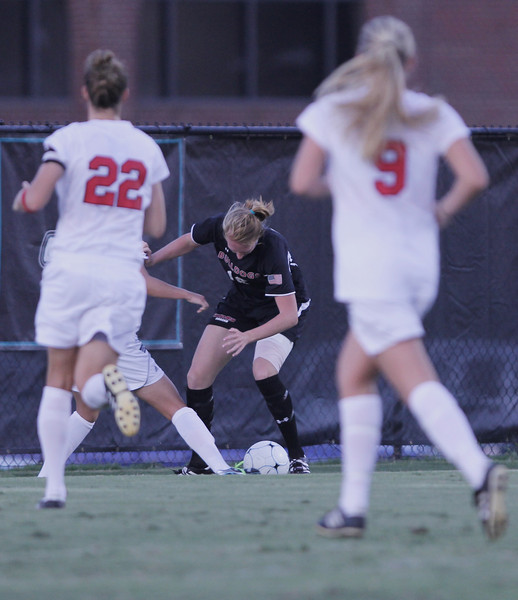 Stephanie Benshoof (16) keeps control of the ball while pushing off a defender.