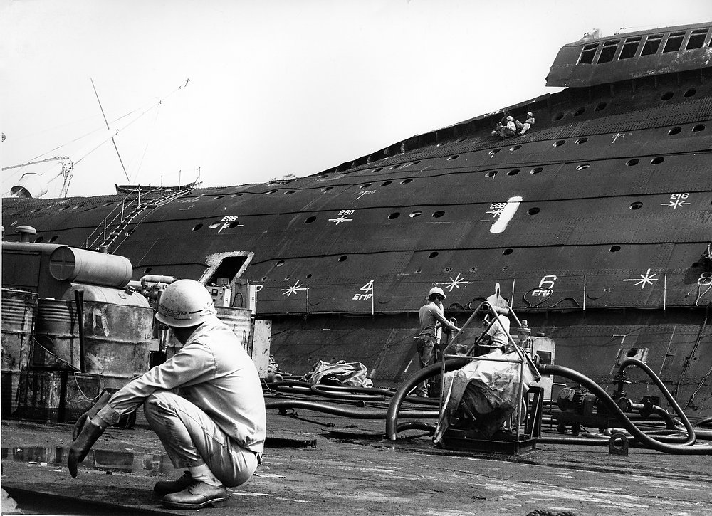 Description of . A member of a Japanese crew removing oil from the wreck of the former Queen Elizabeth squats on a working platform stationed next to the wreck in Hong Kong harbor on Oct. 27, 1972. The picture illustrates how the side of the ship has collapsed inwards with the heat of the fire. The ladder at left leads to what was the bridge area. (AP Photo)