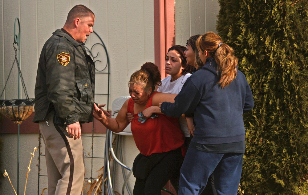. A family member was stopped by a Weld County Sheriff Officer as she runs across police tape, Tuesday, December 18, 2012, where four people were found dead in a home in Longmont. The women was over come with emotion at scene. RJ Sangosti, The Denver Post