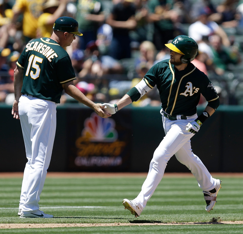 . Oakland Athletics\' Jed Lowrie, right, is congratulated by third base coach Steve Scarsone (15) after hitting a home run off Cleveland Indians\' Dan Otero in the third inning of a baseball game Sunday, July 16, 2017, in Oakland, Calif. (AP Photo/Ben Margot)