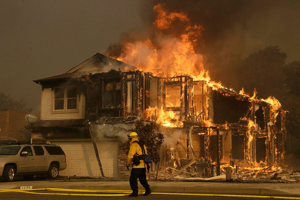 . A firefighters walks near a home in Santa Rosa, Calif., Monday, Oct. 9, 2017. Wildfires whipped by powerful winds swept through Northern California sending residents on a headlong flight to safety through smoke and flames as homes burned. (AP Photo/Jeff Chiu)