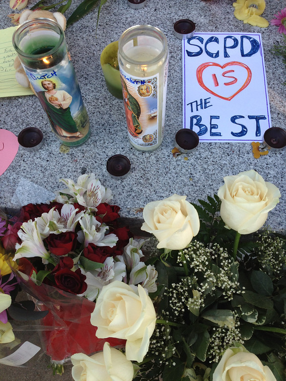 """. Prayer candles burn as part of a memorial at the Santa Cruz Police Department for fallen officers <a href=\""""http://www.santacruzsentinel.com/localnews/ci_22676931\"""">Elizabth Butler</a> and <a href=\""""http://www.santacruzsentinel.com/localnews/ci_22676928\"""">Loran \""""Butch\"""" Baker</a>. The detectives died <a href=\""""http://www.santacruzsentinel.com/ci_22674808\"""">in a shootout Tuesday</a>.(Shmuel Thaler/Sentinel)"""