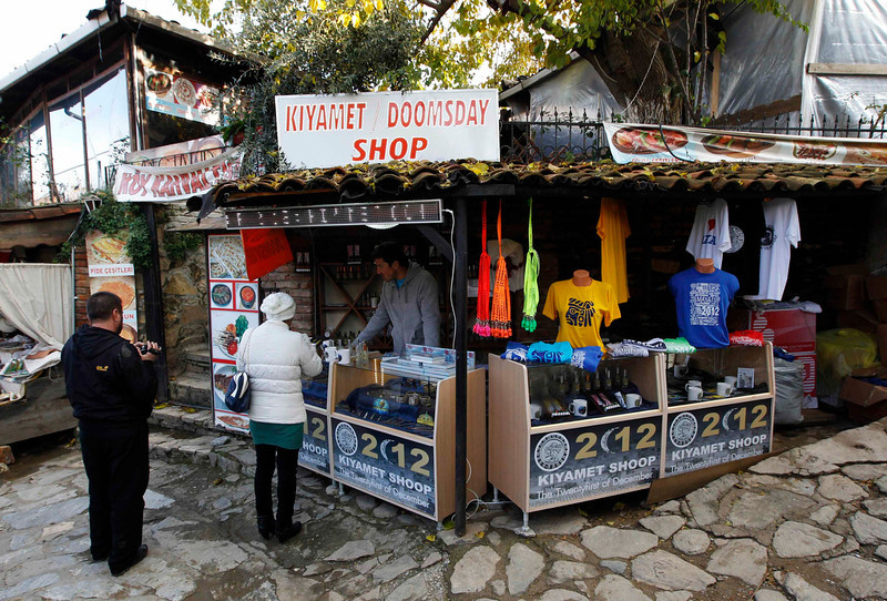 ". People shop at a gift stall in Sirince December 20, 2012. Thousands of foreign and local tourists are expected to flock to Sirince, a small Turkish village near the ancient Greek city Ephesus ruins, which is believed to be one of the few places on earth that will survive December 21, a day in an old Maya calendar dubbed ""the end of the world\"". REUTERS/Osman Orsal"