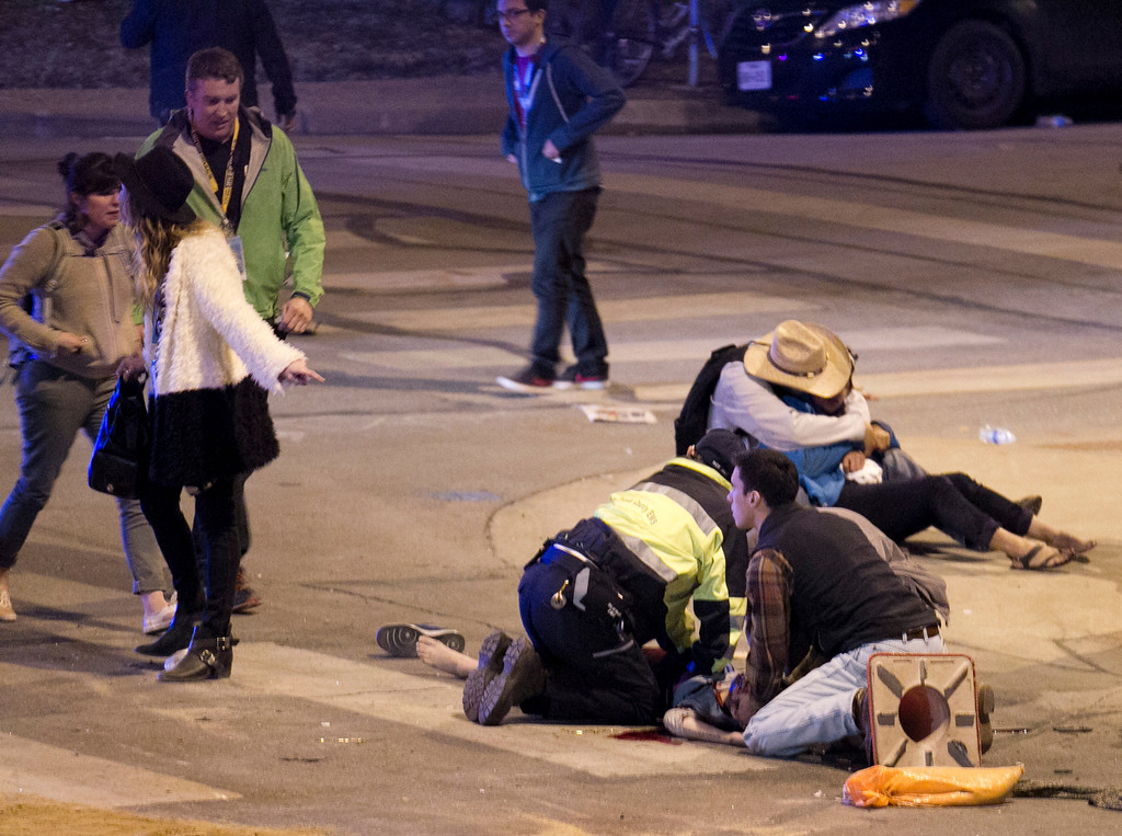 . People perform CPR on a woman after she was struck by a vehicle on Red River Street in downtown Austin, Texas, at SXSW on Wednesday March 12, 2014.  (AP Photo/Austin American-Statesman, Jay Janner)