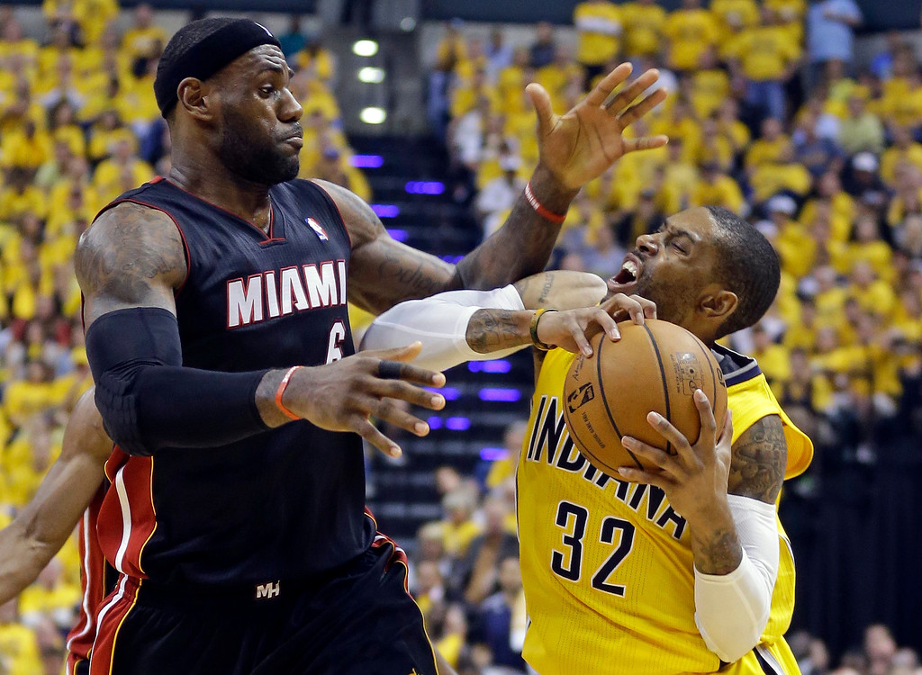 . Miami Heat forward LeBron James, left, fouls Indiana Pacers guard C.J. Watson during the fourth quarter of Game 2 of the NBA basketball Eastern Conference finals in Indianapolis, Tuesday, May 20, 2014. The Heat defeated the Pacers 87-83 to tie the series at 1-1. (AP Photo/Michael Conroy)