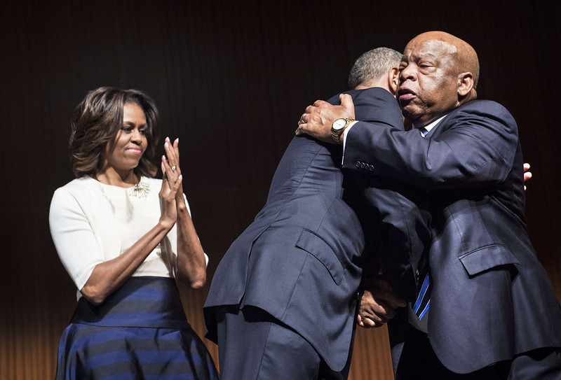 . US First Lady Michelle Obama (L) watches as US President Barack Obama (C) is hugged by Rep. John Lewis (D-GA) at the Lyndon B. Johnson Presidential Library April 10, 2014 in Austin, Texas, during a civil rights summit to celebrate the 50th anniversary of the Civil Rights Act of 1964.  (BRENDAN SMIALOWSKI/AFP/Getty Images)