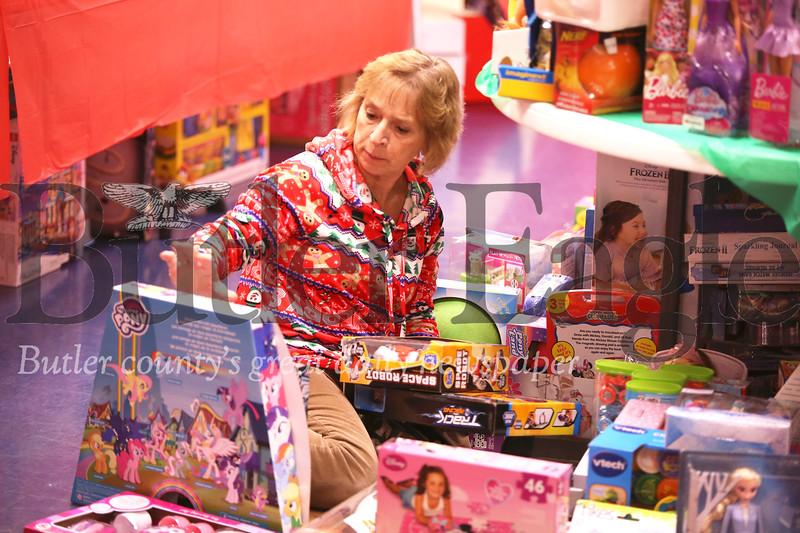 Els Wittlinger of Renfrew sorts through toys Friday night setting up for Saturday's Lighthouse Foundation toy store program. Seb Foltz/Butler Eagle