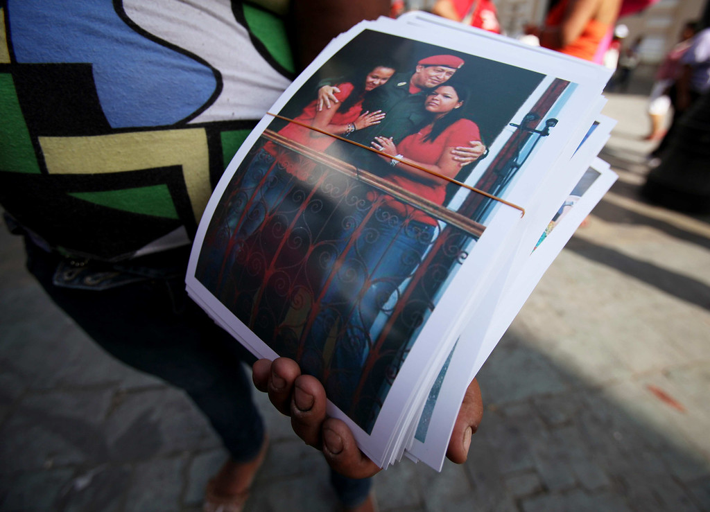 . A street vendor sells photos of Venezuela\'s late President Hugo Chavez with his daughters Maria Gabriela, right, and Rosa Virginia near Bolivar square in Caracas, Venezuela, Monday, March 11, 2013. At Caracas\'s choked Bolivar Plaza, a favorite hangout for the late president\'s supporters, shoppers can find virtually anything Chavez-related the mind can dream up. (AP Photo/Fernando Llano)