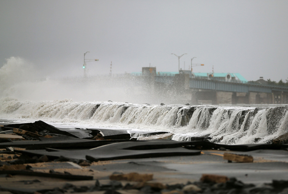 Description of . Heavy surf caused by Hurricane Sandy buckles Ocean Ave on October 30, 2012 in Avalon, New Jersey. The storm has claimed at least 16 lives in the United States, and has caused massive flooding across much of the Atlantic seaboard. US President Barack Obama has declared the situation a 'major disaster' for large areas of the US East Coast including New York City, with wide spread power outages and significant flooding in parts of the city. (Photo by Mark Wilson/Getty Images)