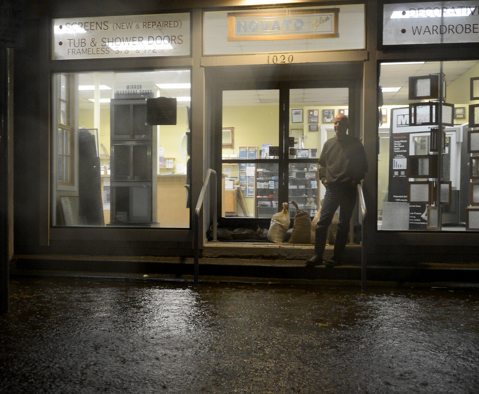 . Novato Glass co-owner Tom Matthews watches flood water levels in front of his business on Reichert Avenue in Novato, Calif., before dawn on Thursday, Dec. 11, 2014. (Alan Dep/Marin Independent Journal)