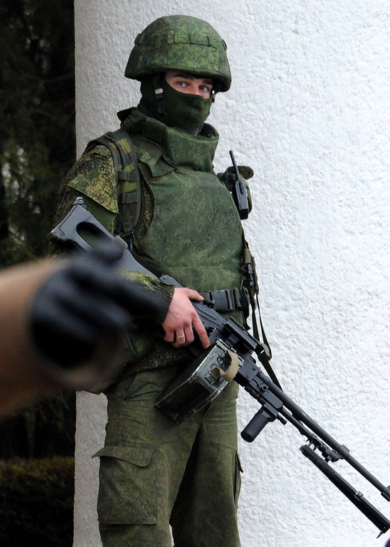 ". One of the unidentified armed men patrols outside of Simferopol airport, on February 28, 2014. Ukraine accused today Russia of staging an ""armed invasion\"" of Crimea and appealed to the West to guarantee its territorial integrity after pro-Moscow gunmen took control of the peninsula\'s main airport.AFP PHOTO / VIKTOR DRACHEV/AFP/Getty Images"