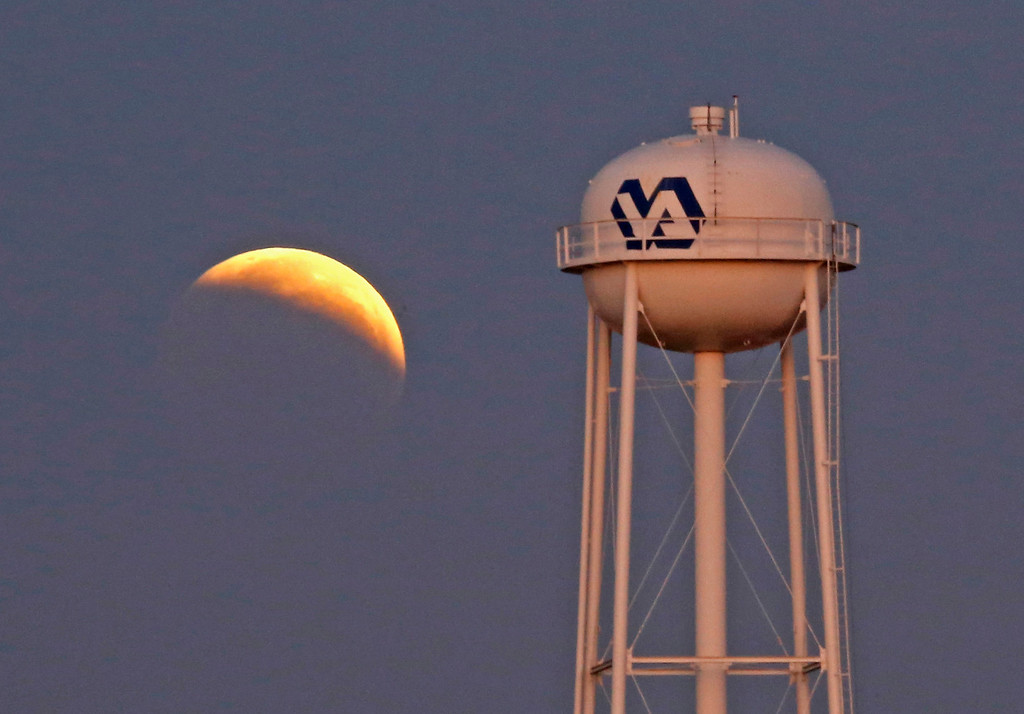. A lunar eclipse appears behind a hospital\'s water tower early Wednesday morning, Oct. 8, 2014 in Jackson, Miss. The moon appears orange or red, the result of sunlight scattering off Earth\'s atmosphere. This is known as the blood moon. (AP Photo/Rogelio V. Solis)