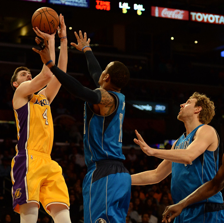 . Los Angeles Lakers forward Ryan Kelly (4) shoots over Dallas Mavericks guard Monta Ellis (11) as Dirk Nowitzki (41) looks on in the first quarter during an NBA basketball game in Los Angeles, Calif., on Friday, April 4, 2014.  (Keith Birmingham Pasadena Star-News)