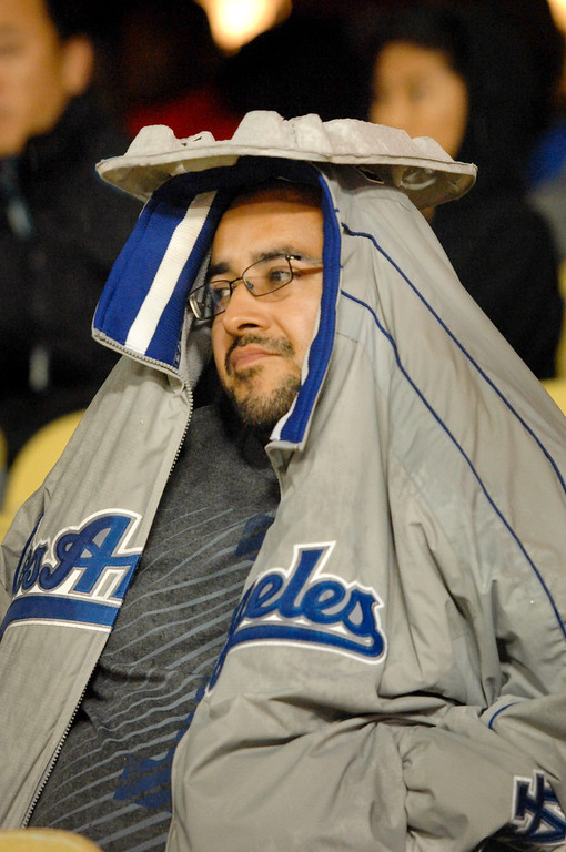 . Raul Guerrero uses a food tray for covering against the rain at the Dodgers-Rockies game, Friday, April 25, 2014, at Dodger Stadium. (Photo by Michael Owen Baker/L.A. Daily News)
