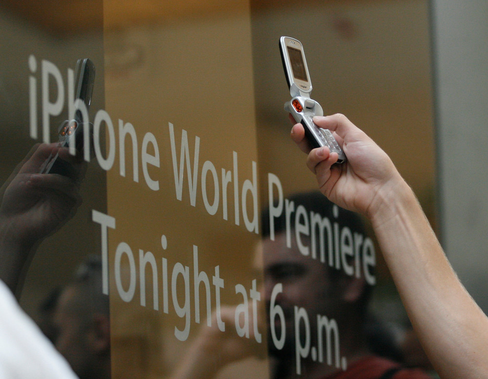 . Drake Orman, 16, of Charlotte, N.C., uses his present camera phone to take a photo through the front of an Apple store as employees inside prepare for the first day of sales for the new Apple iPhone, Friday, June 29, 2007, at Southpark Mall in Charlotte. (AP Photo/Jason E. Miczek).