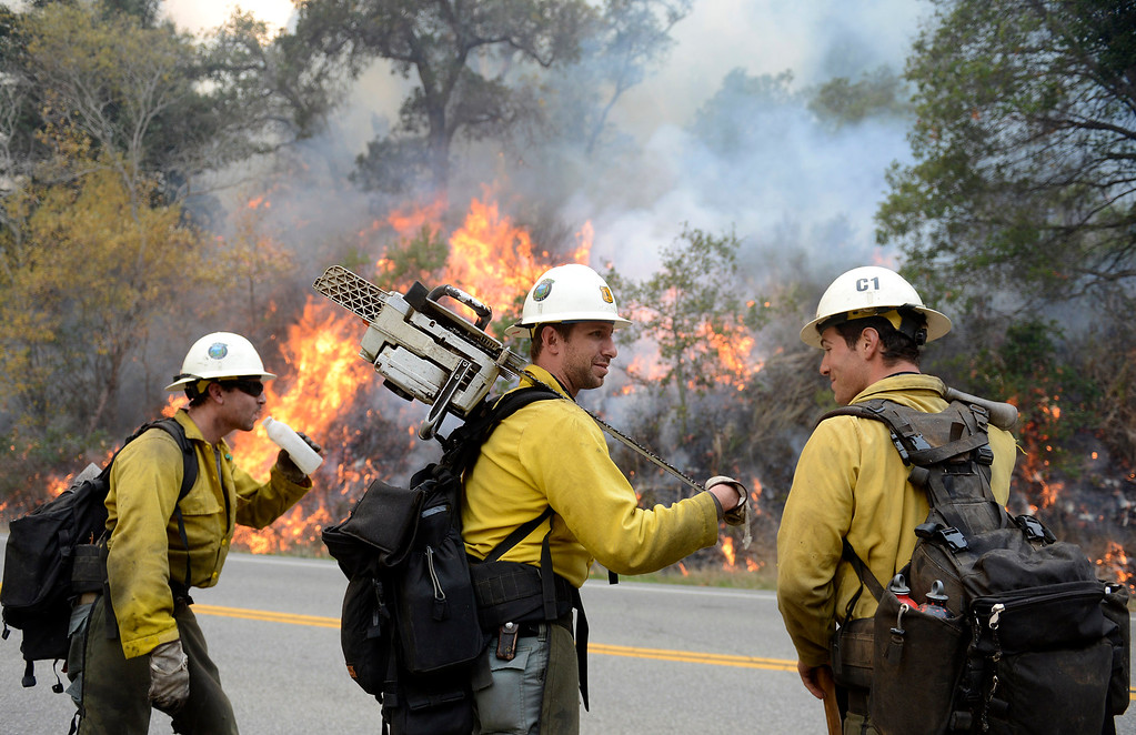 . Los Padres National Forest firefighters Michael Sheppard, left, Tyson Navarro and Alex Woodhull take a break while lighting a back fire along Highway 1 between Pfeiffer Ridge Road and the Big Sur Station in Big Sur, Calif. on Wednesday, December 18, 2013. (Photo David Royal/ Monterey County Herald)