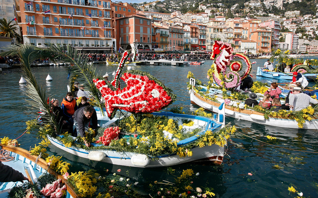 . A fleet of pointus, fishing boats typical of southern France, decorated with locally grown flowers, parade during a naval battle of flowers, in the harbour of Villefranche sur Mer, southeastern France, Monday, Feb. 25, 2013. The sailors file past the public and along the wharves, throwing flowers among the spectators. (AP Photo/Lionel Cironneau)