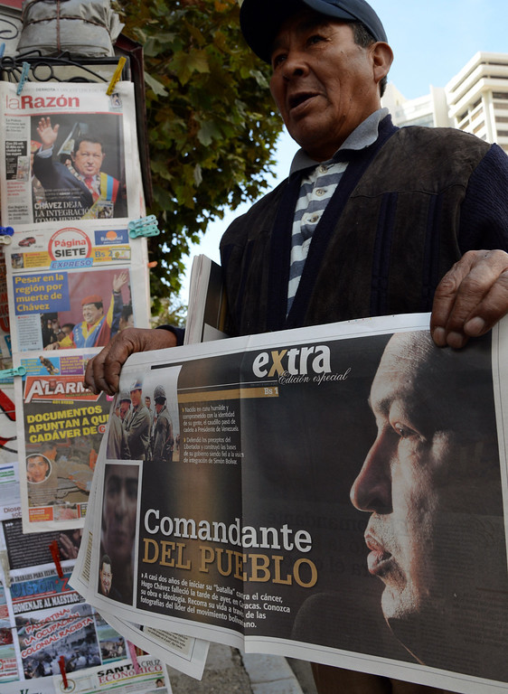 . A newspaper vendor shouts out the latest news showing photographs of late Venezuelan president Hugo Chavez in La Paz on March 06, 2013. Venezuelans began Wednesday to bid farewell to late President Hugo Chavez, whose body was to lie in state for three days to honor the firebrand leftist who ruled the oil-rich nation for 14 years. AFP PHOTO/Aizar  RALDES/AFP/Getty Images