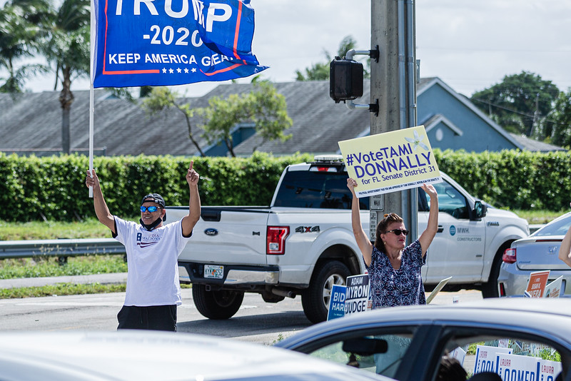 Supporters of President Donald J. Trump wave Trump flags outside the Lantana Road Branch Library in Lake Worth on Election Day, November 3, 2020. (JOSEPH FORZANO / THE PALM BEACH POST)