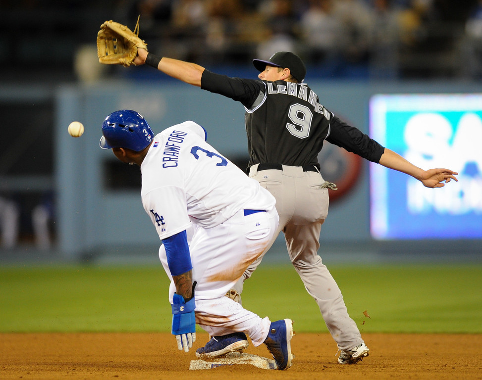 . The Dodgers\' Carl Crawford is safe at second as the Rockies second baseman DJ LeMahieu can\'t field the throw on Juan Uribe\'s infield single in the fourth inning, Friday, April 25, 2014, at Dodger Stadium. (Photo by Michael Owen Baker/L.A. Daily News)